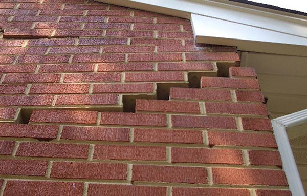 Stair step crack forming at the top of the exterior brick foundation