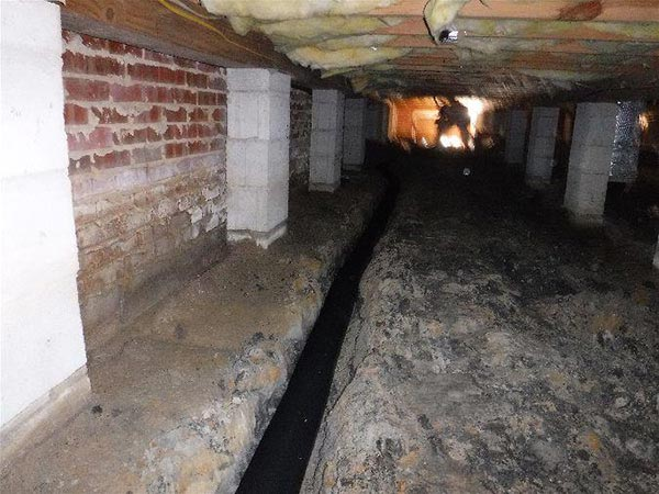 A French Drain Pipe being installed in the foundation of a crawl space
