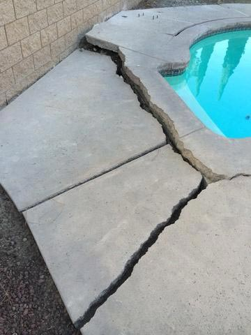 A pool deck that is cracking around the pool and in need of repair